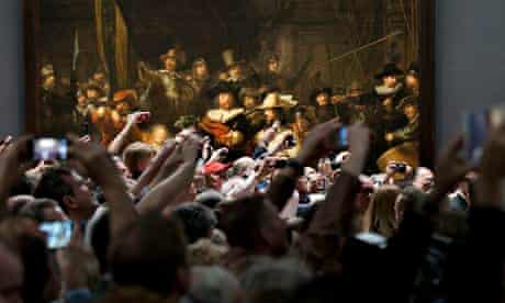 Visitors raise their cameras and mobile phones in front of Dutch master Rembrandt's The Night Watch