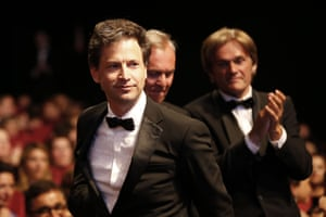 US director Bennett Miller stands up to accept the Award for Best Director for the film Foxcatcher.