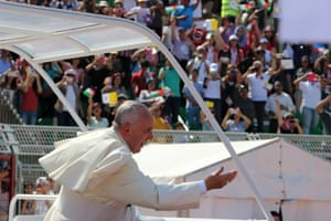 Pope Francis waves to the faithful at a mass at the Amman International Stadium. Pope Francis called for urgent steps to end Syria's three-year-old civil war.