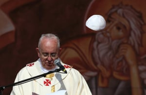 A gust of wind blows off Pope Francis' cap as he speaks during a mass at Amman International Stadium.