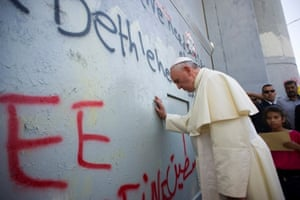 Pope Francis touches the wall that divides Israel from the West Bank, on his way to celebrate a mass in Manger Square.