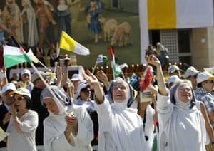 Nuns wave at an open air mass in Manger Square outside the Church of the Nativity in Bethlehem.