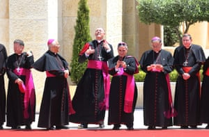 Cardinals wait to welcome Pope Francis at the royal palace in Amman.