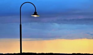Modern designed street lamp with its light on during sunset