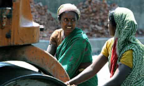 Indian women labourers push a rolling ma