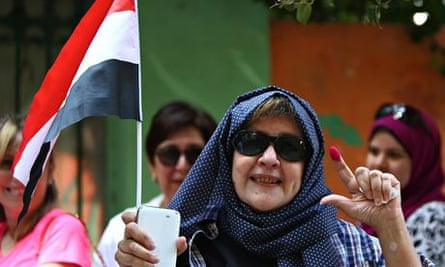 An Egyptian woman displays her ink-stained finger after voting in the presidential election