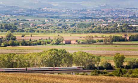 train crosses bridge in Tuscany