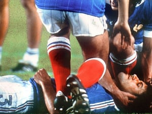 Patrick Battiston lies on the ground as Michel Platini and Didier Six come to his aid.