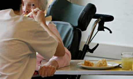 A nurse helps a woman during lunch at a residential home near Lucerne, Switzerland
