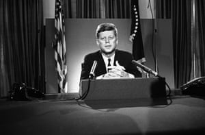U.S. President John F. Kennedy sits behind microphones at his desk in Washington.
