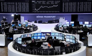 Traders are pictured at their desks in front of the DAX board at the Frankfurt stock exchange May 27, 2014.