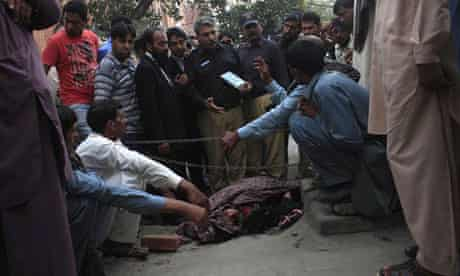 Police collect evidence near the body of Farzana Iqbal outside the Lahore high court building