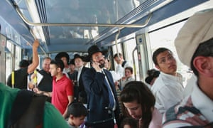 Passengers ride a light rail train in Jerusalem. The route means many of the city's divided residents have to at least tolerate each other for a short journey.