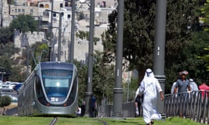 A Muslim man in traditional robes walks on the grass where a light rail passes next to the Old City walls in East Jerusalem.