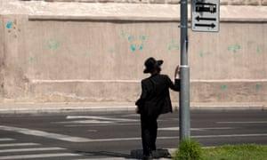 A Jewish ultra-orthodox man stands by a light rail train sign in Jerusalem.