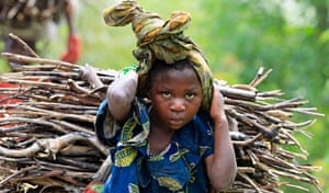 A Congolese girl carries firewood, collected from a forest, in Bunagana town