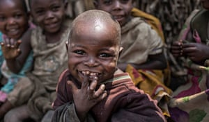 An internally displaced child smiles at the camera during a distribution of tarps in Mubimbi