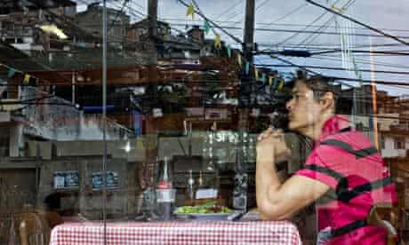 A diner at Bar Lacubaco in the Vidigal favela, reflected in the window. Photograph: Victor R Caivano
