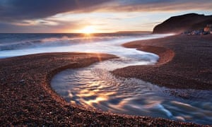 River Winniford flowing into the sea at Seatown Beach in Dorset