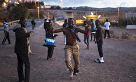 A migrant celebrates after successfully scaling Melilla's border fence.