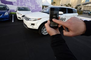 A Valeo representative swipes his finger across an iPhone to initiate a self parking demonstration at the 2014 International CES in Las Vegas, Nevada, January 8, 2014. The car, a Range Rover Evoque with Valeo self-parking technology, is equipped with 12 ultrasonic sensors, six in back and six in front, a laser scanner mounted in the grille, and four cameras.
