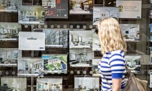 A woman walks past an estate agent in Knightsbridge