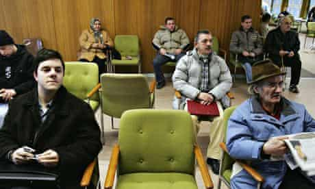 Unemployed people in Berlin wait to receive benefits