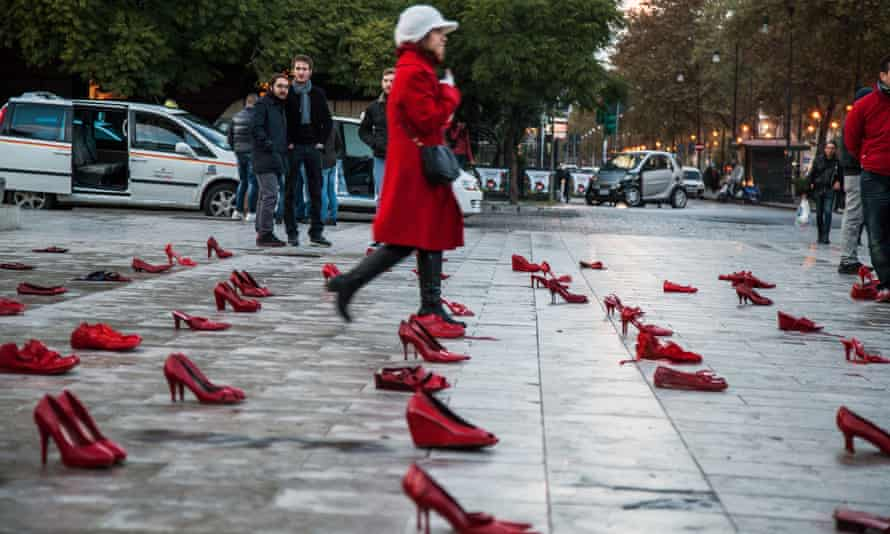 A woman walks past hundreds of red shoes in Palermo, to raise awareness at the violence against women.