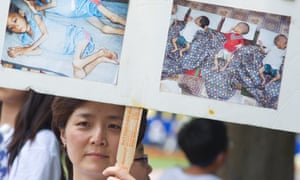 A woman holds up a poster with photos from an internment camp in North Korea during a White House vigil in 2012.