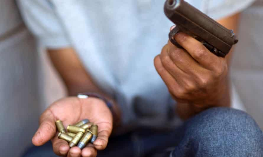 A young gang member shows a gun and ammunition, in Bonteheuwel neighbourhood in Cape Town in 2012.