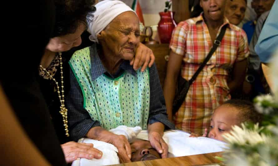 Olga, (c), grandmother of Cameron Fisher, grieves along with relatives over the body of the 21-year-old, as they stand around his coffin, at his home in Bonteheuwel, in 2012, in Cape Town. Fisher, though not an active gang member in the area was aligned to a notorious prison gang, the 28's.