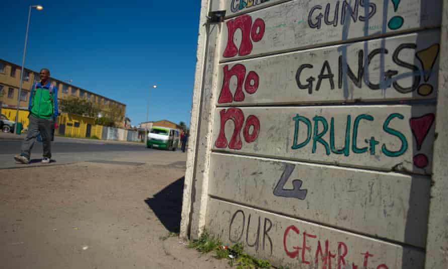 Pedestrians walk past anti-gang graffiti in Manenberg, a township of Cape Town, South Africa, in 2013.