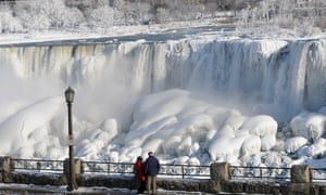 A couple looks at the frozen U.S. Niagara Falls from Canada on January 9, 2014 in Ontario.