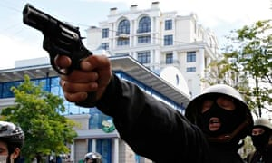 A pro-Russian activist aims a pistol at supporters of the Kiev government during clashes in Odessa