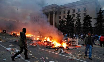 A protester walks past a burning pro-Russia tent camp near the trade union building in Odessa
