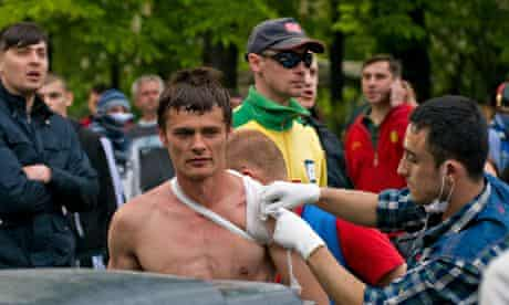 A wounded man takes treatment after clashes in Odessa