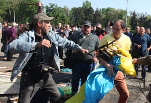 Pro-Russian activists beat a pro-Ukraine supporter trying to save the Ukrainian flag removed from a flagpole outside the burned trade union building in Odessa on May 3, 2014.