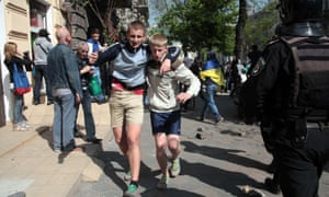 A young man helps another one during clashes between pro-Ukraine football fans and pro-Russian separatists on May 2, 2014 in Odessa.