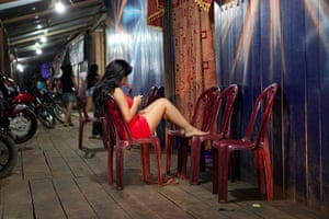 Illegal gold mining: A nightclub worker sits outside a club