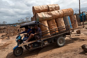 Illegal gold mining: People transport empty drums