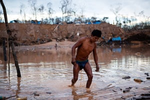 Illegal gold mining: A miner leaves an area where water is pumped