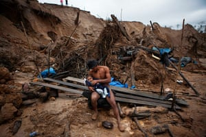 Illegal gold mining: Manuel Espinosa holds his 4-month-old son