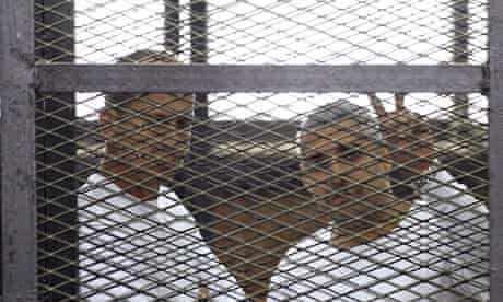 Al-Jazeera journalists Peter Greste and Mohamed Famy in a cage in a court in Cairo, Egypt
