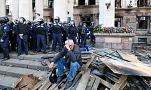 A man sits outside the trade union building where a deadly fire occurred in Odessa