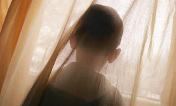 Unidentifiable child looking out of a window
