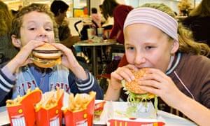 Children eating McDonald's Big Mac hamburgers England UK