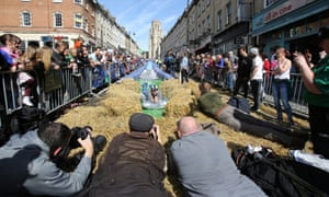 A participant on a lilo slides down a giant water slide that has been installed down Park Street