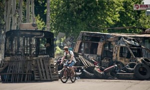 A cyclist passes burned-out buses in Kramatorsk