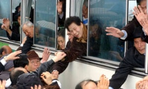 South Koreans in a bus wave to North Korean relatives before they return to South Korea, after the an organised family reunion meeting in 2003.