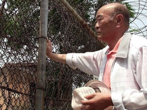 A South Korean, Lee In-Sub, 72, left all his family behind him in North Korea when he fled south during the Korean War. Here he looks to North Korea through a barbed-wire near the DMZ in 2000.